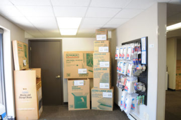 Clean indoor office with moving boxes and other supplies for sale