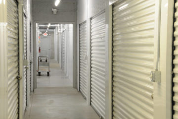 Clean indoor hallway of storage units with white doors