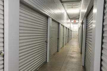 Clean, well-lit hallway of indoor storage units with white doors