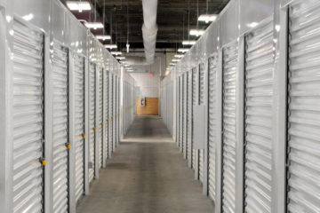 Well-lit, indoor hallway of white storage units